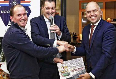 Voorzitter Tim van Zeben en Zeehaven-directeur Peter van de Meerakker overhandigen het eerste boek Noordzeevis uit IJmuiden aan wethouder Jeroen Verwoort (rechts)